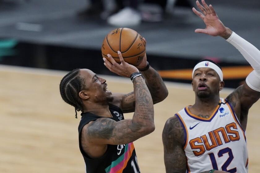 Spurs forward DeMar DeRozan attempts a shot over Suns forward Torrey Craig.