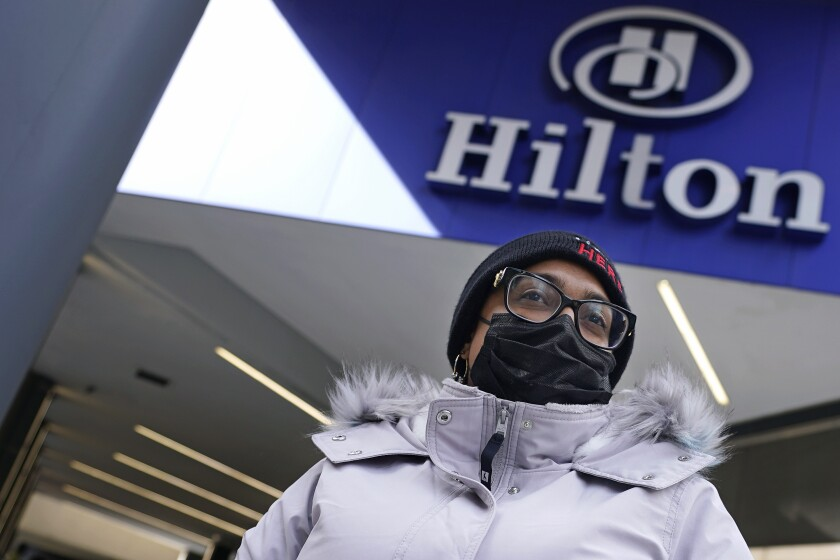 Hotel housekeeper Esther Montanez poses outside the Hilton Back Bay, Friday, March 5, 2021, in Boston. Montanez refuses to give up hope of returning to her cleaning job at the hotel, which she held for six years until being furloughed since March 2020 due to the COVID-19 virus outbreak. (AP Photo/Charles Krupa)
