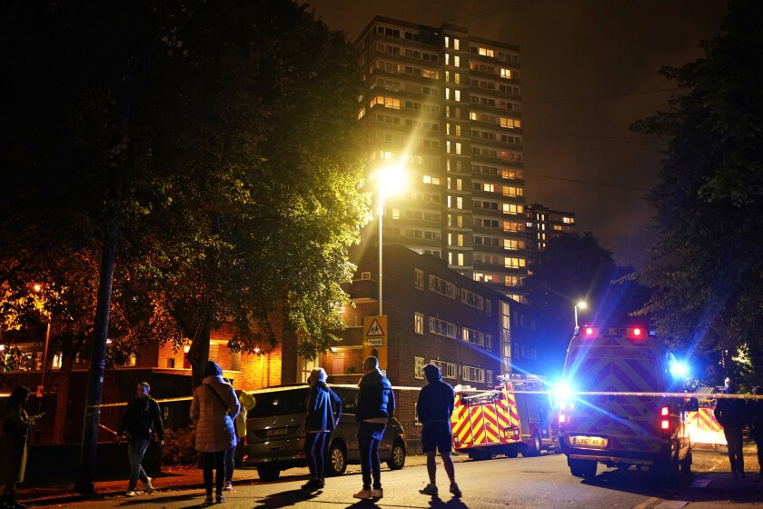 Firefighters and emergency crews work a the scene of a fire at a tower block on Westbridge Road in Battersea, southwest London, on Tuesday, Oct. 12, 2021. A fire erupted on the 20th floor of the apartment building in southwest London on Tuesday evening, causing dozens of residents, including children in pajamas, to flee the tower and injuring one woman and a child, authorities said. (Aaron Chown/PA via AP)