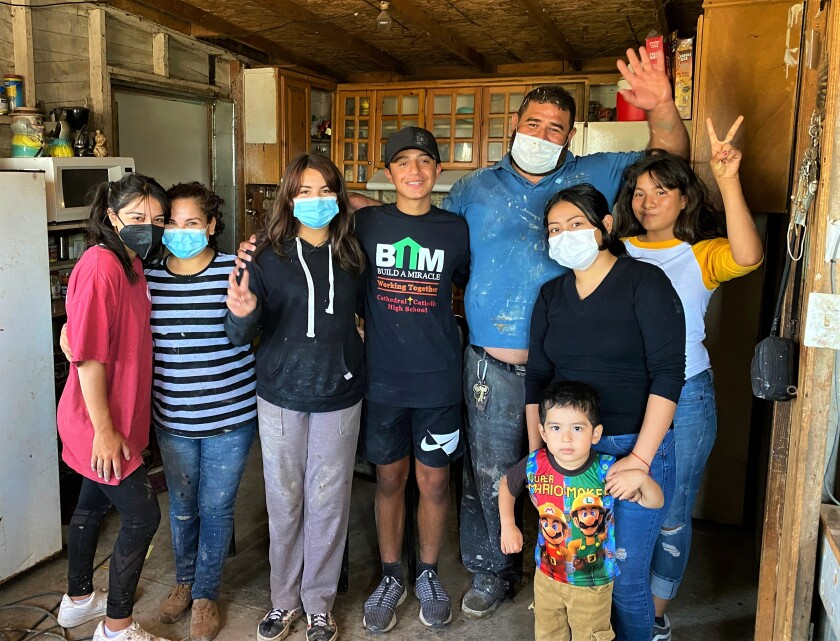 Daniella Benítez and Gabriel pose with a Tijuana family whose house they started to build