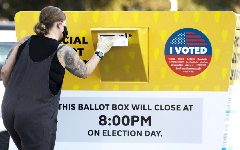 =A woman drops off her ballot at an Official Ballot Drop Box located near the Rose Bowl in Pasadena, CA October 13, 2020. =
