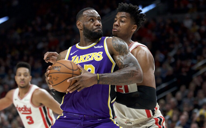 Lakers forward LeBron James drives down the lane against Trail Blazers center Hassan Whiteside during the first half of a game on Dec. 28, 2019, in Portland.