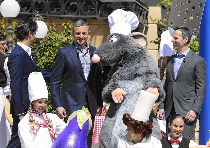 """Disney CEO Robert Iger, center, and Chief Operating Officer Thomas Staggs, right, inaugurate a """"Ratatouille"""" attraction at Disneyland Paris in 2014."""