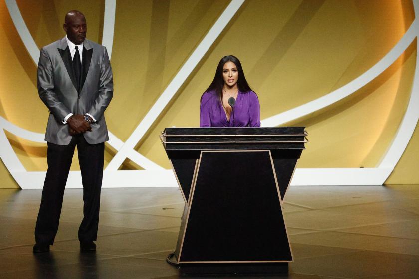 Vanessa Bryant speaks at a podium as Michael Jordan looks on