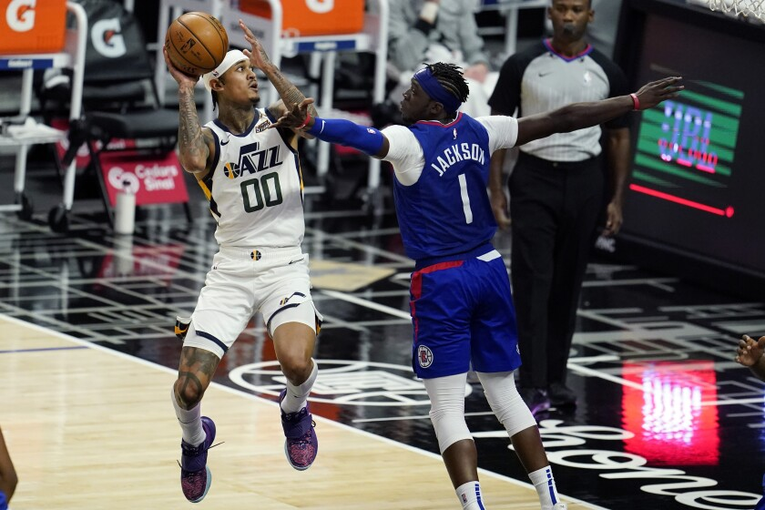 Jordan Clarkson, base del Jazz de Utah, dispara frente a Reggie Jackson, de los Clippers de Los Ángeles