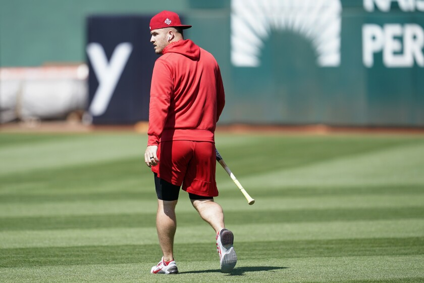 Mike Trout in red shorts and a hoodie walks across a field holding a bat