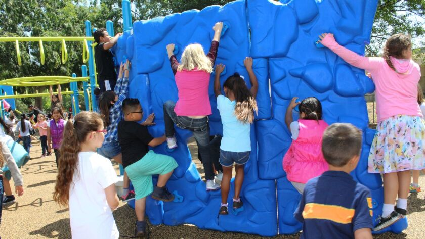 Ramona Elementary students climb the wall of the school's new playground.