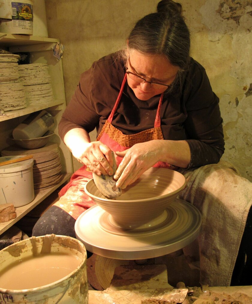 This Oct. 18, 2013 photo shows potter Diana Johnston at work in her studio in Mineral Point, Wis. Johnston lives with her husband, Tom, in the malting tower of an old brewery which they have converted into an enormous pottery studio. The couple are part of a thriving community of artists who live and work in this former lead mining town. (AP Photo/Helen O'Neill)