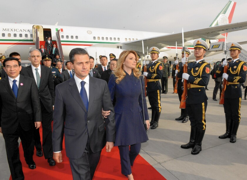 """Mexican President Enrique Pena Nieto and wife Angelica Rivera arrive in Beijing. The president """"absolutely"""" had to fly to China for a trade mission, an aide said."""