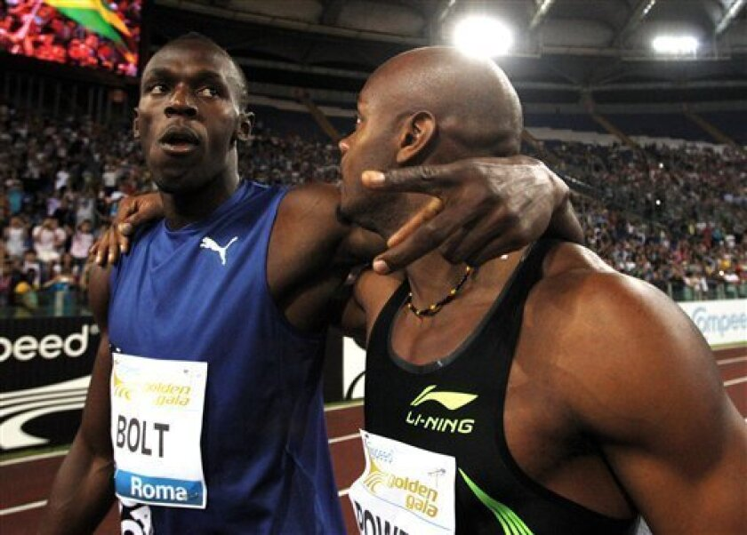 FILE - The May 26, 2011 file photo shows Jamaica's Asafa Powell, right, celebrating with his fellow-countryman Usain Bolt following the men's 100 meters event at the Golden Gala athletics meeting, in Rome. On Thursday, Aug 25, 2011 Asafa Powell has been ruled out of the 100 meters at the world championships because of a groin injury, eliminating defending champion Usain Bolt's biggest rival from the marquee event. (AP Photo/Andrew Medichini)