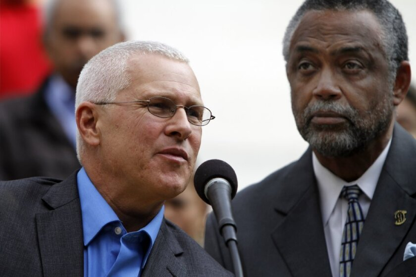 Los Angeles City Councilmen Mike Bonin, left, and Curren Price Jr. are seen speaking last month outside City Hall about their proposal to raise the minimum wage for some L.A. hotel workers to about $15 an hour.