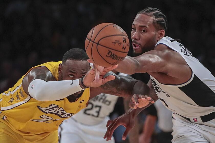 LeBron James and Kawhi Leonard chase after a loose ball.
