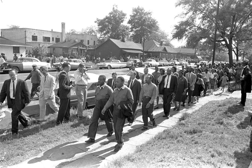 The Rev. Ralph Abernathy, left, and the Rev. Martin Luther King Jr. lead a column of demonstrators