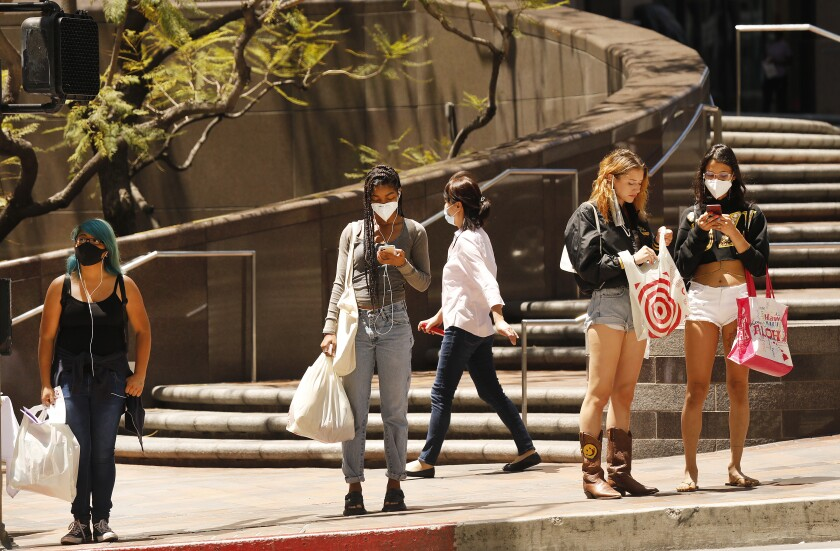 Shoppers carry purchases made Tuesday at Fig at 7th, an open-air mall in downtown Los Angeles.