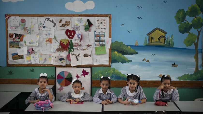 File - In this Wednesday, Aug. 29, 2018 file photo, girls sit inside a classroom at an UNRWA school