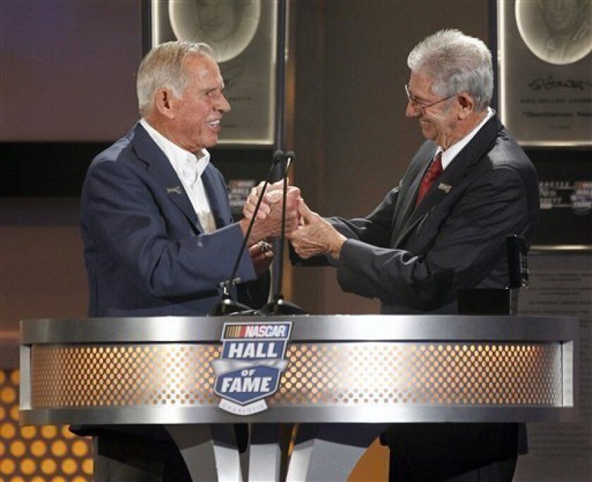 David Pearson, left, reacts as he is inducted into the NASCAR Hall of Fame by team owner Leonard Wood, right, in Charlotte, N.C., Monday, May 23, 2011. (AP Photo/Terry Renna)