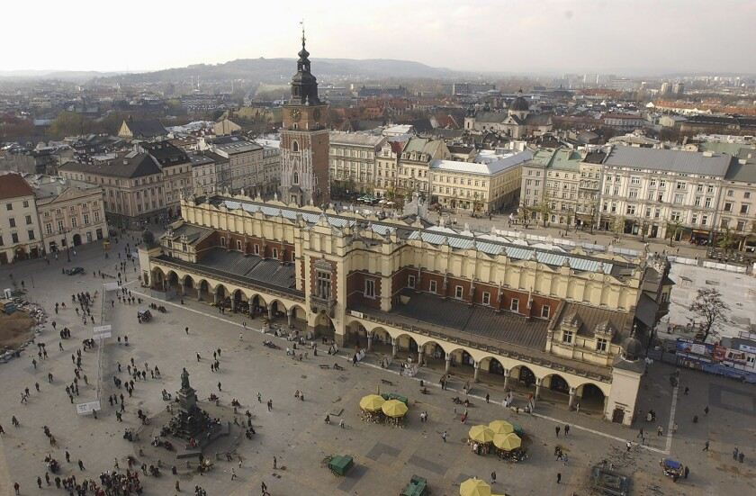 FILE - In this file photo taken on Nov. 3, 2004, A view of the Polish city of Krakow and its roofed cloth market, or Sukiennice, seen from the taller tower of St. Mary's Basilica. Every hour, a trumpeter plays the city's trademark bugle call from the tower's windows. Officials said Thursday, May 6, 2021, that the team of trumpeters, who are retired firefighters, was recently reinforced with two new players. (AP Photo/Czarek Sokolowski, file)