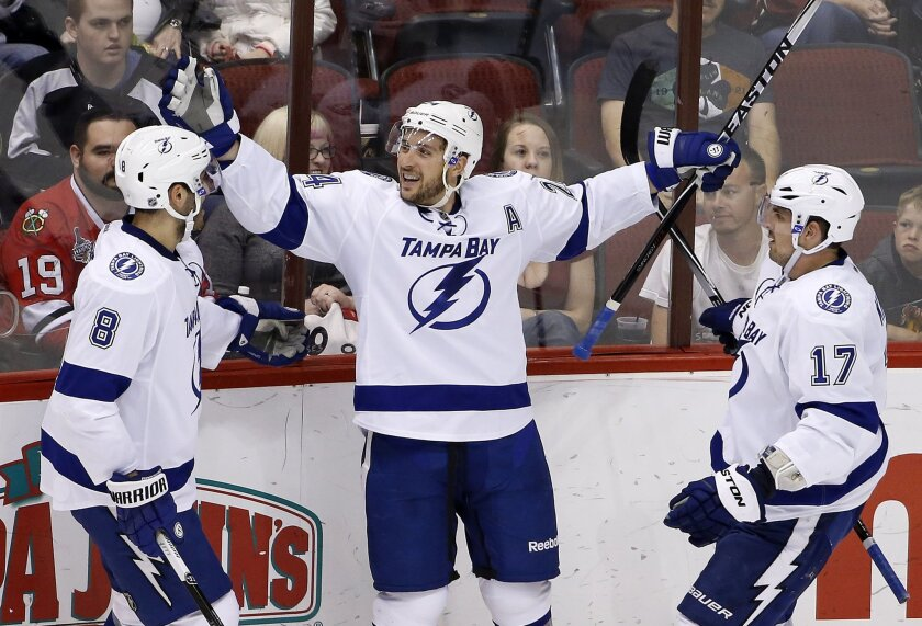 Tampa Bay Lightning's Ryan Callahan, middle, celebrates his goal against the Arizona Coyotes with teammates Mark Barberio (8) and Alex Killorn (17) during the second period of an NHL hockey game Saturday, Feb. 21, 2015, in Glendale, Ariz. (AP Photo/Ross D. Franklin)