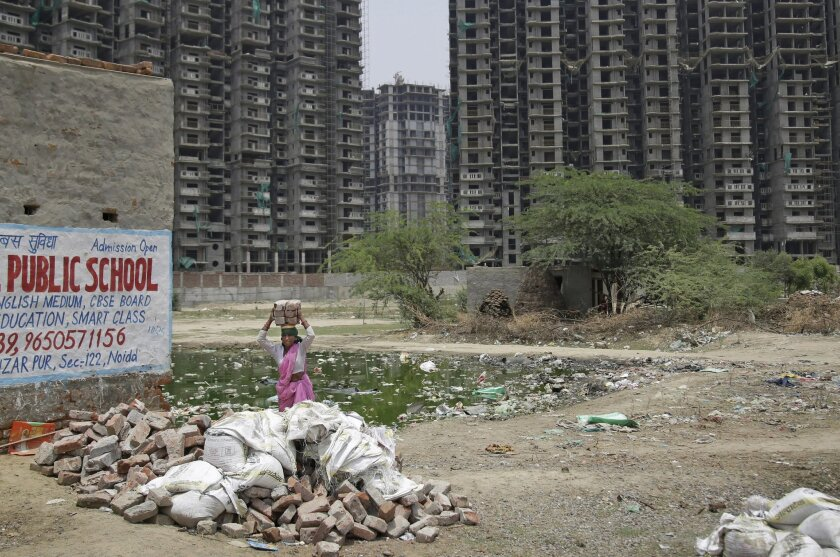 A construction worker carries bricks on her head at a site in the Noida suburb of New Delhi, India, Tuesday, May 31, 2016. The UN's mid-2016 report on the World Economic Situation and Prospects released earlier this month expects India to grow by 7.3 per cent this year and 7.5 per cent next year, t