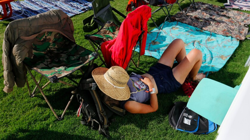 A concertgoer takes a rest on the grounds of the Desert Trip festival in Indio.