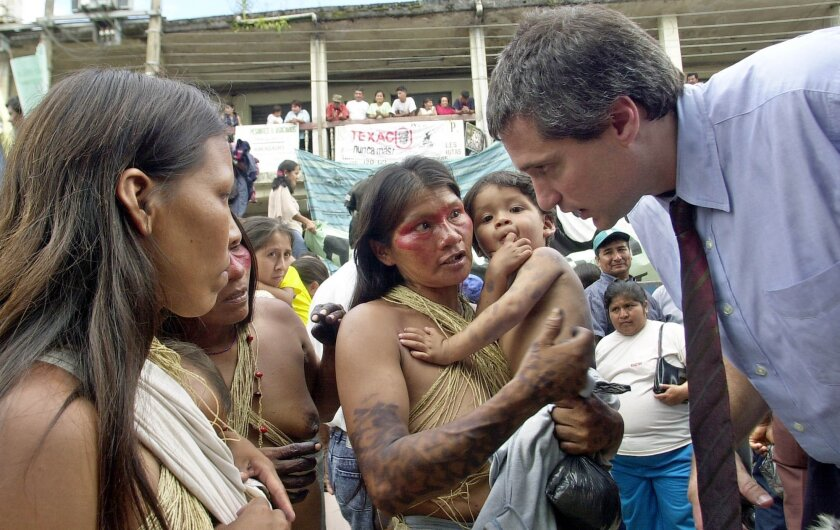 Lawyer Steven Donziger, right, speaks to Huaorani women during this first day of the trial in Ecuador in October 2003. The case is in its 23rd year and hearings have been held on three different continents. (AP Photo/Dolores Ochoa)