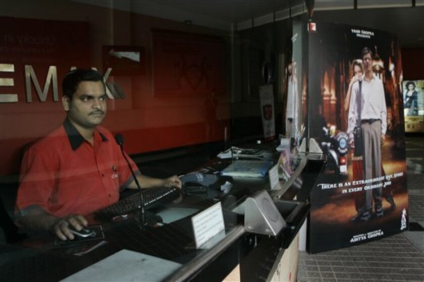 Ticket booking officer waits for customers at a theater in Mumbai, India, Wednesday, Dec. 10, 2008. With Mumbai still mourning its recent terror attacks, Bollywood faces a balancing act of showing solidarity with the residents of India's entertainment heartland, while gently nudging locals back into movie theaters to boost an industry already hurt by the global economic downturn. (AP Photo/Rajanish Kakade)