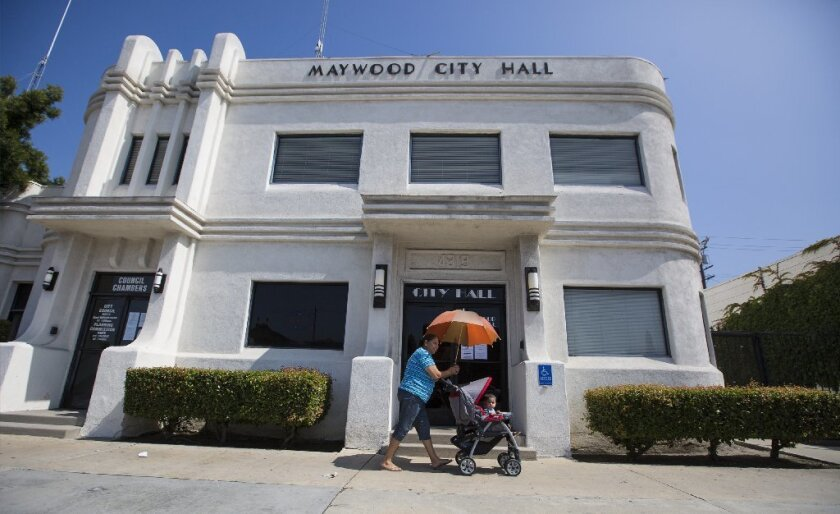 Una mujer y su hija pasan frente al ayuntamiento de Maywood.