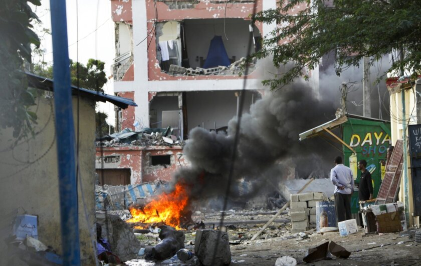 Somali men watch as fires burn amidst the destruction outside the Sahafi Hotel in Mogadishu, Somalia Sunday, Nov. 1, 2015. A Somali police officer says an explosion followed by heavy gunfire has been heard, thought to have been caused by a suicide car bomb, at the hotel often frequented by Somali g