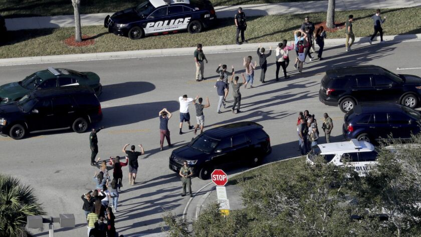Students are evacuated by police from Marjory Stoneman Douglas High School in Parkland, Fla., after a shooter opened fire on the campus on Feb. 14.
