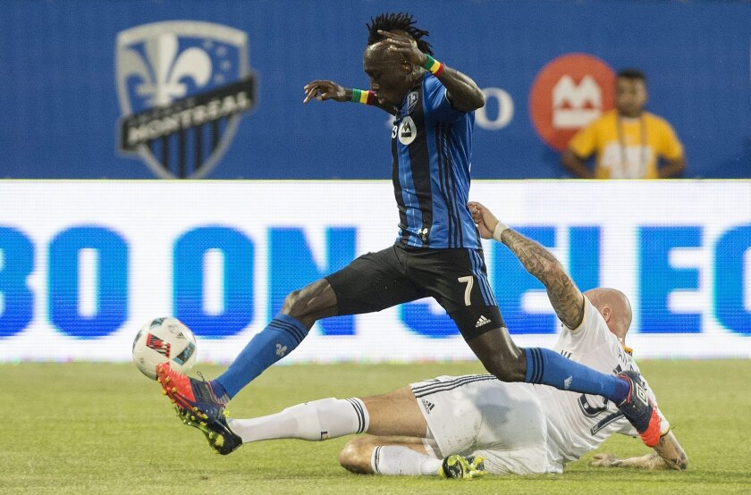 Montreal Impact's Dominic Oduro (7) challenges Los Angeles Galaxy's Jelle Van Damme during first-half MLS soccer game action in Montreal, Saturday, May 28, 2016. (Graham Hughes/The Canadian Press via AP) MANDATORY CREDIT