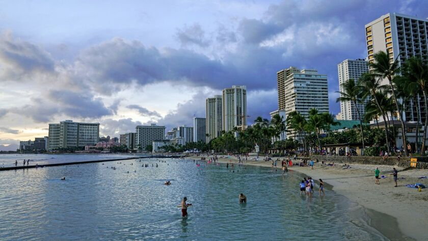 HONOLULU, HI - AUGUST 20: People enjoy the beach, as the sun sets off of Waikiki Beach, on Monday, A