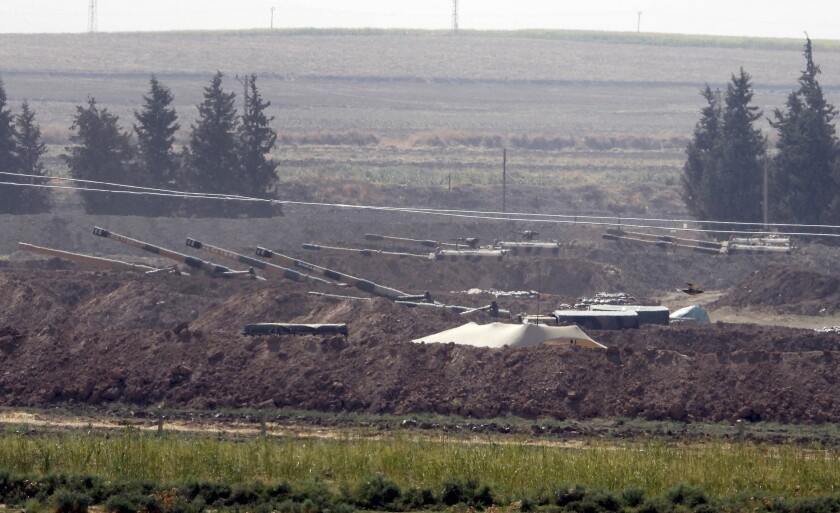 In this Sunday, Oct. 6, 2019 photo, Turkish forces artillery pieces are seen on their new positions near the border with Syria in Sanliurfa province, Turkey. U.S.-backed Kurdish-led forces in Syria said American troops began withdrawing Monday from their positions along Turkey's border in northeastern Syria, ahead of an anticipated Turkish invasion that the Kurds say will overturn five years of achievements in the battle against the Islamic State group. (DHA via AP)