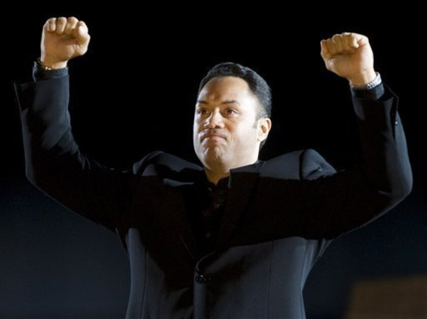 This April 4, 2008 file photo shows former Toronto Blue Jays player Roberto Alomar gesturing to the crowd as he is honored prior to the Blue Jays' home opener against the Boston Red Sox, in Toronto. (AP Photo/The Canadian Press, Adrian Wyld, File)