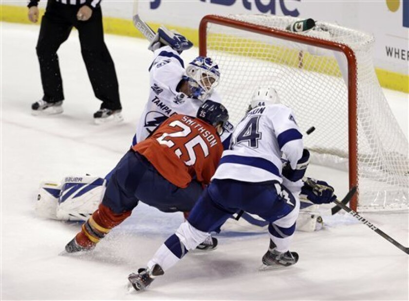 Florida Panthers' Jerred Smithson (25) scores the game tying goal, 3-3, against Tampa Bay Lightning goalie Anders Lindback (39) as Nate Thompson (44) defends in the second period of an NHL hockey game in Sunrise, Fla., Saturday, Feb. 16, 2013. (AP Photo/Alan Diaz)