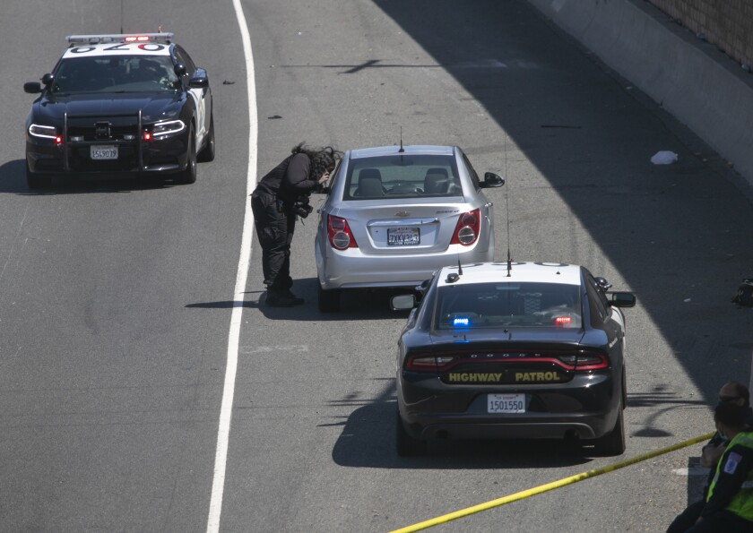 A crime scene investigator photographs the Chevy Cruze sedan with a bullet hole in the hatch.