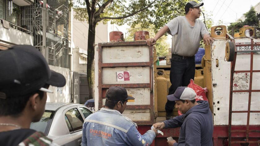 A costumer (right) pays for the gas canister to Jorge Alberto Rodriguez while Agustín Martinez looks