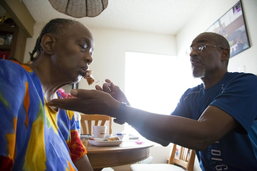 Alford Claiborne feeding his wife, Rita, who has Alzheimer's Disease.