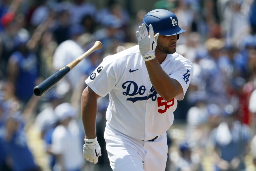 Los Angeles Dodgers' Albert Pujols throws his bat after hitting a two-run home run against the Los Angeles Angels during the second inning of a baseball game in Los Angeles, Sunday, Aug. 8, 2021. (AP Photo/Alex Gallardo)