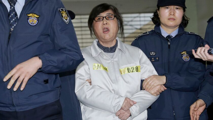 Choi Soon-sil, center, the jailed confidant of impeached South Korean President Park Geun-hye, shouts upon her arrival at the office of the independent counsel in Seoul on Jan. 25, 2017.