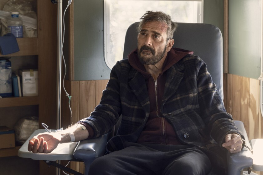 Jeffrey Dean Morgan as a battered and bearded Negan sits in a chair with tubes attached to his arm.