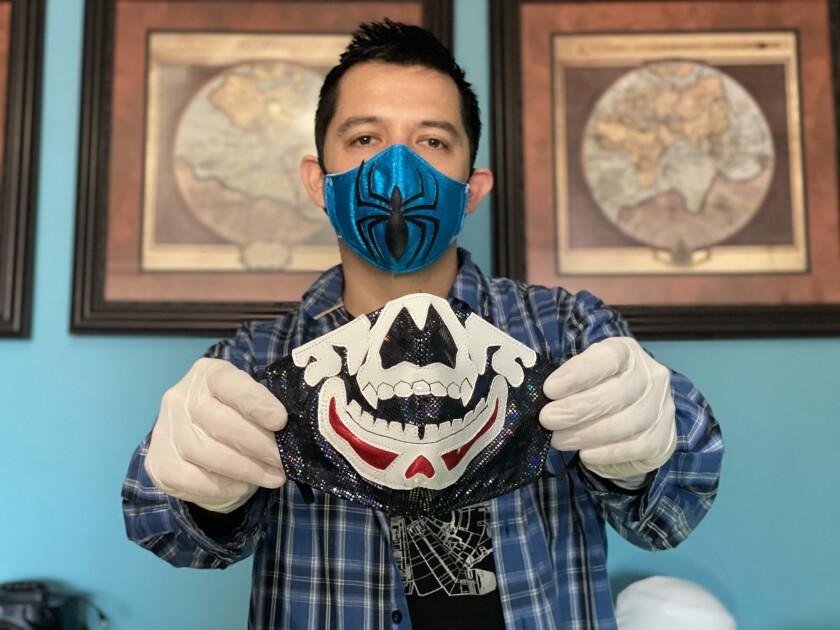El mascarero Abraham Pacheco, 37, muestra uno de sus cubrebocas de lucha libre \.