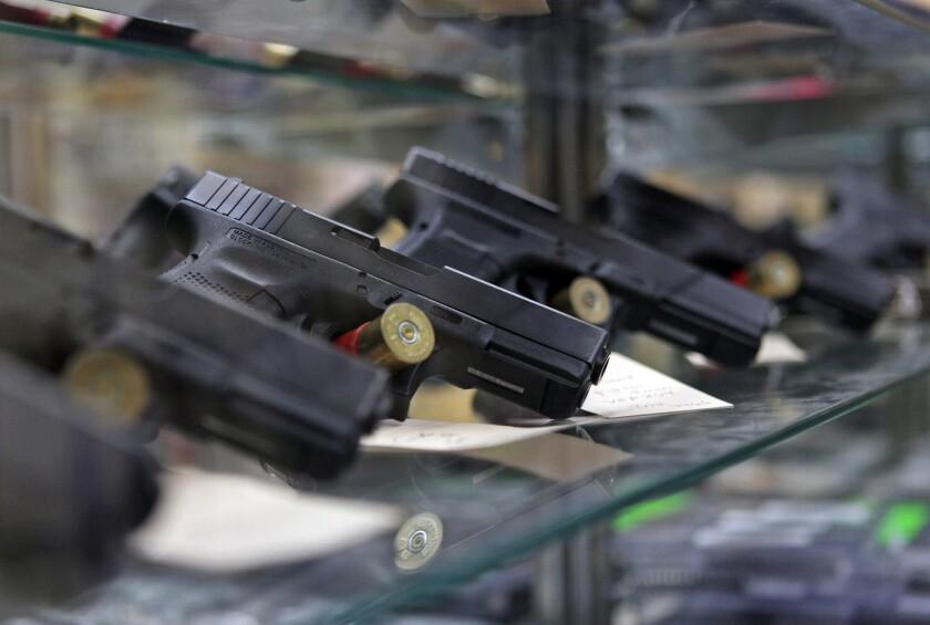 Glock pistols sit on display in a glass case at the Article 2 Gun Store in Lombard, Ill.