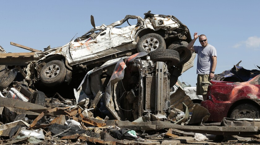 Eric Lowery looks at tornado-ravaged vehicles while retrieving items from his mother's car at a destroyed strip mall. Cleanup continues two days after a huge tornado roared through the Oklahoma City suburb of Moore.