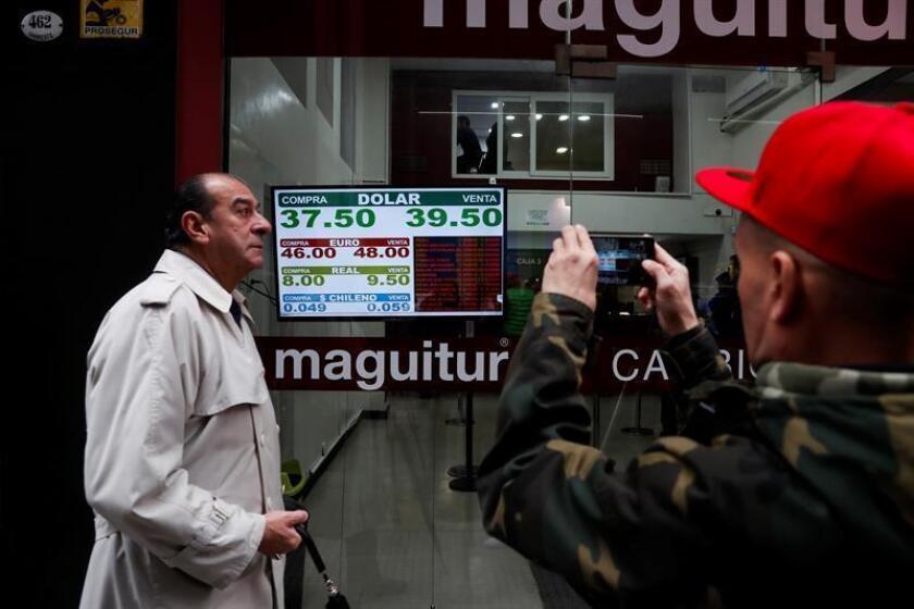 """Imagen del jueves 30 de agosto de 2018, donde transeúntes observan y fotografían los paneles de las casas de cambio en el centro de Buenos Aires (Argentina). Los ciudadanos de Argentina no están """"acostumbrados"""" a las crisis económicas, pero las tienen que pasar y hacer un esfuerzo para ayudar a su país a salir adelante, dijo hoy Ezequiel Sabor, embajador de Argentina en México. EFE/ARCHIVO"""