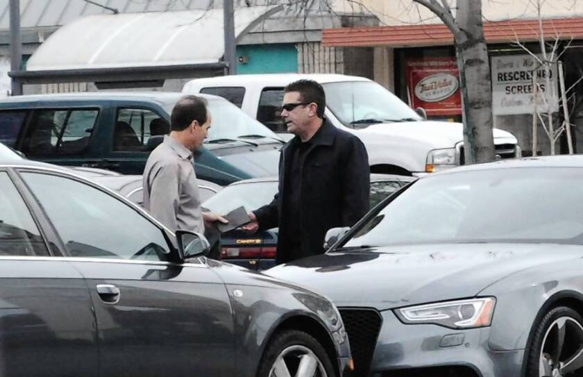 KPMG partner Scott London, left, is shown in FBI photograph allegedly accepting a $5,000 bribe from Bryan Shaw.