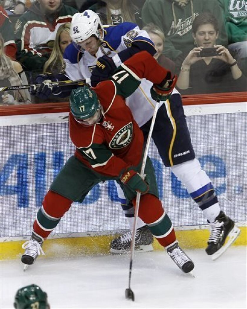 Minnesota Wild left wing Torrey Mitchell (17) controls the puck as St. Louis Blues center David Backes (42) tries to get at it during the first period of an NHL hockey game in St. Paul, Minn., Monday, April 1, 2013. (AP Photo/Ann Heisenfelt)