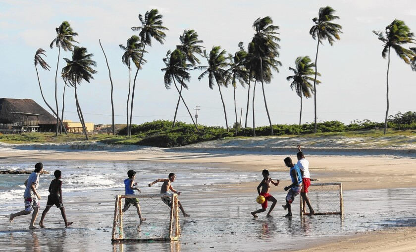 Children plan on a beach north of Natal, Brazil. Natal is one of the host cities of the FIFA World Cup 2014. It is also a city that has been known as a hub for sex tourism, though the government is fighting to reduce that problem.