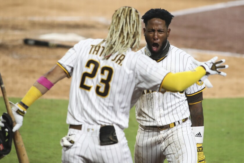 San Diego Padres' Jurickson Profar, right, reacts after scoring on a fielder's choice in the seventh inning of a baseball game against the Los Angeles Dodgers, Monday, Sept. 14, 2020, in San Diego. (AP Photo/Derrick Tuskan)