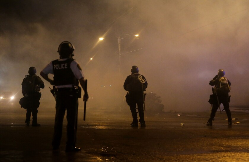 Law enforcement officers watch early Sunday as canisters are fired to disperse a Ferguson, Mo., crowd defying a midnight curfew to protest the fatal shooting of Michael Brown.