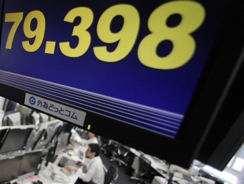 Money traders work under a screen flashing the U.S. dollar against the Japanese yen at a foreign exchange in Tokyo, Japan, Wednesday, July 13, 2011. The dollar fell against yen following worries over Europe's debt crisis. (AP Photo/Itsuo Inouye)